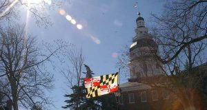 Maryland flag backlit by the sun outside of the Statehouse. (The Daily Record / Maximilian Franz)