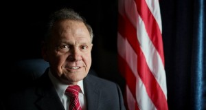 In this Feb. 17, 2015, file photo, Alabama Chief Justice Roy Moore poses in front the the American flag in Montgomery, Ala. The chief justice continues to fight against gay marriage in Alabama. Moore has been suspended from office after the Judicial Inquiry Commission accused him of violating the canons of judicial ethics with his actions during the fight over same-sex marriage. (AP Photo/Brynn Anderson, File)
