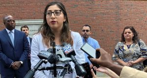 Lilian Calderon answers questions during a lunch break outside federal court, Monday, Aug. 20, 2018, in Boston, as her husband, Luis Gordillo, center back, and others stand nearby.  (AP Photo/Philip Marcelo)