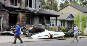 Federal Aviation Administration officials investigate the scene of a plane crash in Payson, Utah on Monday. Authorities say the small plane has crashed into a house in Utah, killing the pilot. (Scott G Winterton/The Deseret News via AP)
