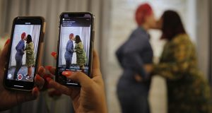 """Cynthia Sanchez takes video and pictures as her sister Jennifer Escobar, right, and Luz Sigman kissing during their May 8, ,2020, wedding ceremony at Vegas Weddings in Las Vegas. Now, the state that's home to the self-proclaimed """"wedding capital of the world"""" is the first in the country to officially protect same-sex marriage in its constitution. (AP Photo/John Locher, File)"""