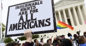 Protesters gather on Oct. 8, 2019, outside the Supreme Court in Washington where the Supreme Court is hearing arguments in the first case of LGBT rights since the retirement of Supreme Court Justice Anthony Kennedy.  As vice president in 2012, Joe Biden endeared himself to many LGBTQ Americans by endorsing same-sex marriage even before his boss, President Barack Obama. Now, as president-elect, Biden is making sweeping promises to LGBTQ activists, proposing to carry out virtually every major proposal on their wish lists.   (AP Photo/Susan Walsh, File)