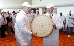 Judges Robert Aschebrock, left, and Bill Schlinsog carry the world's best cheese, a Gruyere by Cedric Fragniere of Switzerland.