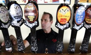 In this July 25, 2011 photo, Flying Dog Brewery CEO Jim Caruso selects a beer to pour from a tap at the brewery's headquarters in Frederick. (AP Photo/Patrick Semansky)