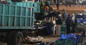 Sanitation workers remove debris from the Occupy Baltimore site after police evicted occupiers from McKeldin Square in Baltimore, Tuesday, Dec. 13, 2011.  Baltimore City police moved into McKeldin Square around 3:30 a.m. and closed off surrounding streets. (AP Photo/Patrick Semansky)