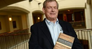 Professor William L. Reynolds poses with the book he co-authored, 'Injustice on Appeal: The United States Courts of Appeals in Crisis,' at the University of Maryland Francis King Carey School of Law.