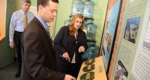 As Van Reiner, president and CEO of the Maryland Science Center, looks on, Michael Hudak and Anne Deady of the MSBA Leadership Academy check out the exhibit that the academy has placed at the center to increase awareness of the dwindling oyster population in the Chesapeake Bay.
