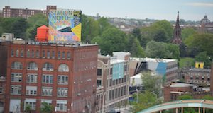 A sign denoting the Station North Arts and Entertainment District sits atop the Copycat Building, a former industrial warehouse turned artist housing project. (Josh Cooper/The Daily Record)