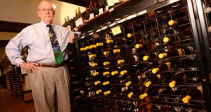 Michael Hyatt, president of Wells Discount Liquors on York Road, poses with a wine display that has a message: TAX. His proximity to Baltimore County presents a big challenge to sales.