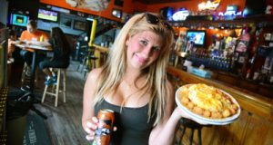 Rachel Sheubrooks, owner of Sliders Bar & Grill near Camden Yards, holds an Orioles-themed can of National Bohemian beer and a Baltimore Tots appetizer. 'The better [the Orioles] do, the busier we are,' she says.