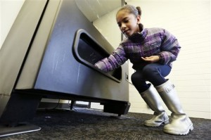 In this Dec. 23, 2013 photo, a 12-year-old girl, who declined to be identified, reaches for the drink she purchased at a vending machine in Seattle. Office workers in search of snacks will be counting calories along with their change under new labeling regulations for vending machines included in President Barack Obama's health care overhaul law. The Food and Drug Administration, which is expected to release final rules early next year, says requiring calorie information to be displayed on roughly 5 million vending machines nationwide will help consumers make healthier choices. (AP Photo/Elaine Thompson)