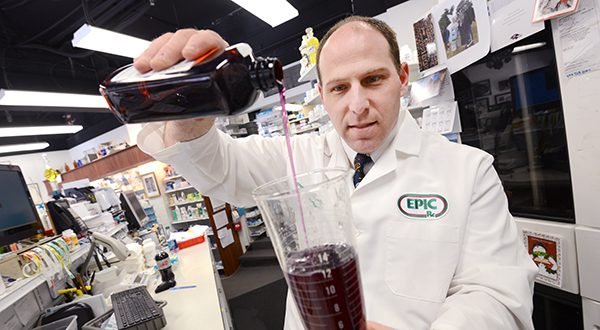 Stephen Wienner, owner and pharmacist at Mt. Vernon Pharmacy, pours and counts some generic pharmaceuticals. (The Daily Record/Maximilian Franz)