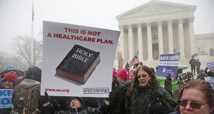 Beth Corbin holds a poster during a demonstration in front of the Supreme Court on Tuesday as the court heard oral arguments in the challenges to President Barack Obama's health care law requirement that businesses provide their female employees with health insurance that includes access to contraceptives. Supreme Court justices are weighing whether corporations have religious rights that exempt them from part of the new health care law that requires coverage of birth control for employees at no extra charge. (AP Photo)