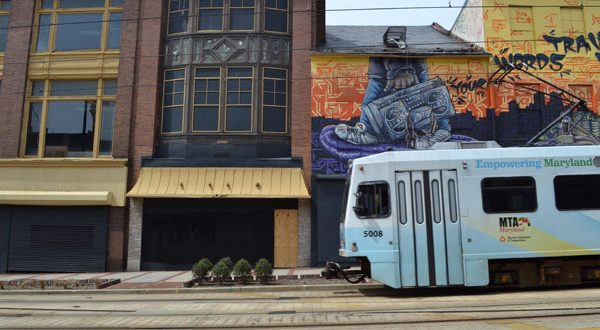 A Light Rail train passes by city-owned properties in the 400 block of North Howard Street that Baltimore wants to redevelop. (The Daily Record/Adam Bednar)