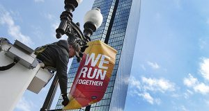 Last month, a worker hangs a banner announcing the Boston Marathon on a lamppost along Boylston Street in Boston. This year's race is projected to bring in $175 million in economic activity to the region, topping last year by at least $35 million. (AP Photo)