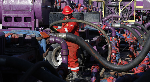 A worker adjusts hoses during a hydraulic fracturing operation at an Encana Corp. oil well, near Mead, Colo. (AP Photo/Brennan Linsley)
