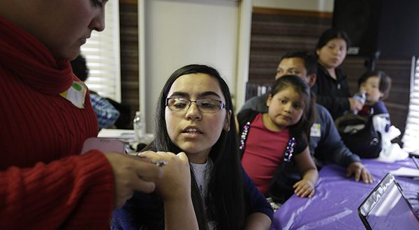 Lorena Amaya, second from left, 13, is given assistance by a family member during a health care enrollment event at the Bay Area Rescue Mission Monday, March 31, 2014, in Richmond, Calif. Whether it's a chance for a subsidy or to avoid a tax penalty, Californians are making a last-minute dash to sign up for health coverage. Midnight marks the enrollment deadline under President Barack Obama's health reform law. Covered California, the state's insurance exchange, is reporting a final surge after it already had enrolled more than 1 million people for individual policies. (AP Photo/Eric Risberg)