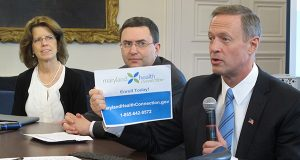 Gov. Martin O'Malley holds up a phone number for people to call to get help enrolling in health insurance in the state's health care exchange on Friday, March 28, 2014 in Annapolis, Md. While the state's online exchange still has serious technology glitches, O'Malley says more people have been able to get through in recent weeks after improvements were made. Dr. Joshua Sharfstein, Maryland's health secretary is seated next to O'Malley, and Carolyn Quattrocki, the interim director of the exchange, is next to Sharfstein. (AP Photo/Brian Witte)