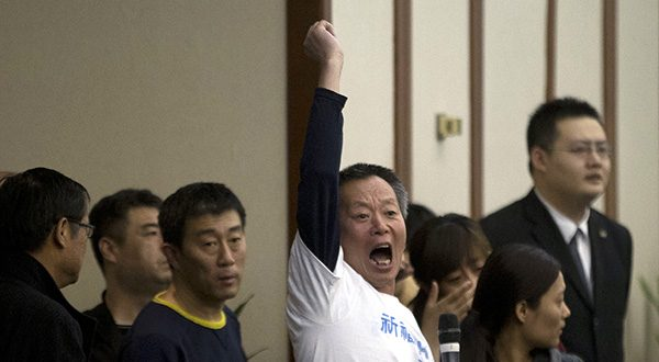 A relative of Chinese passengers aboard the missing Malaysia Airlines, flight MH370, protests after Malaysian government representatives leave after a briefing in Beijing, China. (AP Photo/Ng Han Guan)