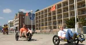 Beachgoers wheel their way down Ocean City's boardwalk with some of the city's hotels in the background. (File Photo)