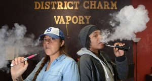 Owners of District Charm Vapory, Laura Greeley, left, and Rachel R. Alexander, smoke from a few of the vaporizers they sell in their store in Pigtown. (The Daily Record/Maximilian Franz)