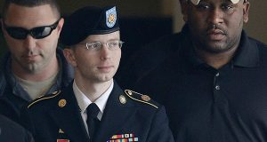 Then-Army Pfc. Bradley Manning, who has since changed her name to Chelsea Manning, is escorted to a security vehicle outside a courthouse in Fort Meade, Md., after a court martial hearing in August 2013. (AP Photo/Patrick Semansky, File)