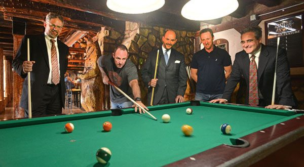 Co-owner Scott Steele relaxes with a game of pool after regaining control of The Lodge. He's joined by (from left) attorneys David Daneman and Albert 'Jay' Young, co-owner David Steele and attorney Martin H. Schreiber II, who helped the Steele brothers in the legal fight. (The Daily Record/Maximilian Franz)