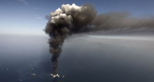 On April 21, 2010, oil can be seen in the Gulf of Mexico, more than 50 miles southeast of Venice on Louisiana's tip, as a large plume of smoke rises from fires on BP's Deepwater Horizon offshore oil rig. (AP Photo/Gerald Herbert, File)
