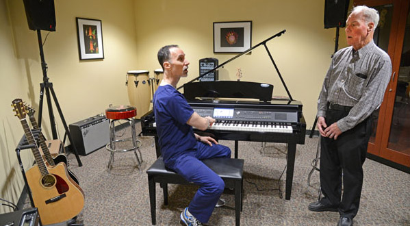 Dan Sherwood, Senior speech pathologist at the Johns Hopkins Voice Center at GBMC, left, conducts an acoustical voice evaluation with patient and classical singer Francis Gilbert French. (The Daily Record/Maximilian Franz)