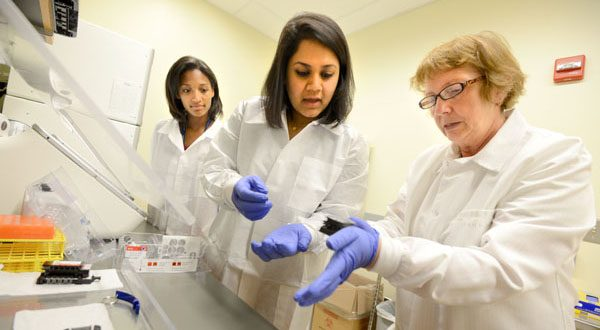From left to right, University of Maryland School of Medicine students Piper Carroll and Richa Kalsi are instructed by clinical research assistant Marcella Lambros on how to test blood samples to look for mutations. (The Daily Record/Maximilian Franz)