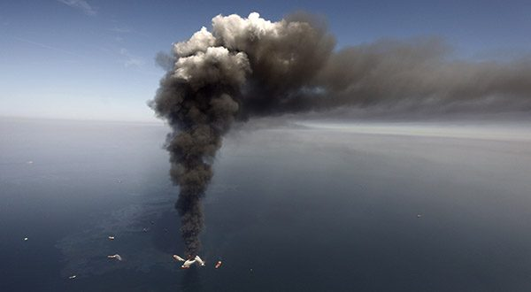 Oil can be seen in the Gulf of Mexico, more than 50 miles southeast of Venice on Louisiana's tip, as a large plume of smoke rises from fires on BP's Deepwater Horizon offshore oil rig. (AP Photo/Gerald Herbert, File)