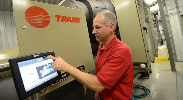 Jeff Blankman, sustainable manufacturing manager for McCormick and Company, inside of a new chiller unit, demonstrates how to navigate the touch screen instrument panel. The 750-ton chiller is 75 percent more efficient than the direct expansion units it replaced at the 600,000-square-foot McCormick factory. Blankman is part of a corporate movement toward greater social responsibility.