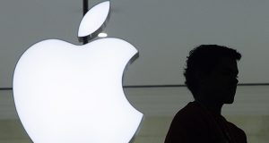 A person stands near the Apple logo at the company's store in Grand Central Terminal, in New York. (AP Photo/Mark Lennihan, File)