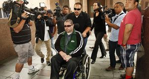 A wheelchair bound Bryan Stow, assisted by a caregiver, is surrounded by family and media as he is led into the Los Angeles County Superior Courthouse in downtown Los Angeles, Wednesday, June 25, 2014. (AP Photo/Los Angeles Times, Al Seib)