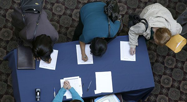 Job seekers sign in before meeting prospective employers during a career fair at a hotel in Dallas. The U.S. economy finally regained the jobs lost during the Great Recession, but the comeback is far from complete. (AP Photo/LM Otero)