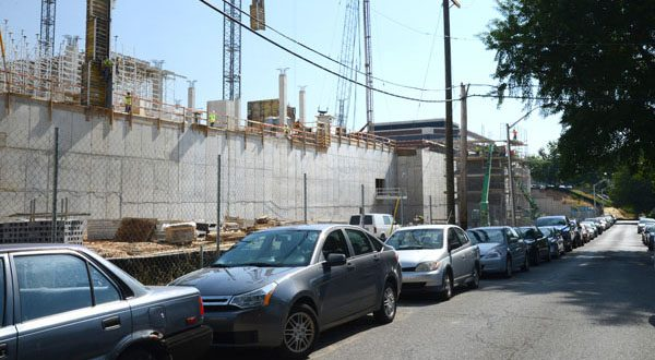 The construction at the Rotunda on 40th Street has led to a proposal to restrict parking. A sign points to where customers should park while they patronize businesses in Hampden Village. Cars line 38th Street behind the construction site. (The Daily Record/Maximilian Franz)