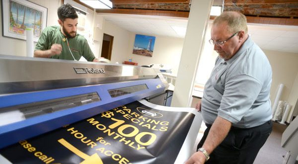 Graphic designer David Lustic, left, and Vince Poist print out signs for a parking lot. (The Daily Record/Maximilian Franz)
