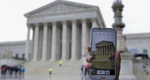 A Supreme Court visitor takes pictures with her cell phone during April's hearing on whether police may search cell phones found on people they arrest without first getting a warrant. (AP Photo)