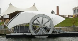The water wheel in the Inner Harbor removes trash by using booms to funnel tdebris to a conveyor. with contributions this month of $11,680 from the Baltimore Water Taxi and $10,000 each from the Canton Car Wash and 1212 East Apartments, The Waterfront Partnership has reached nearly 40 percent of its goal of $550,000 to build another water wheel in Canton. (The Daily Record/Maximilian Franz
