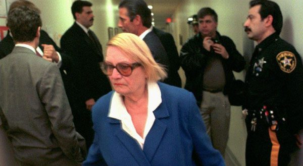 Vera Coking walks past Donald Trump, partially obscured against wall at left, in a courtroom hallway at Atlantic County Superior Court in 1997. (AP Photo)
