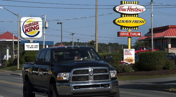 A Burger King sign and a Tim Hortons sign are displayed in Lower Sackville, Nova Scotia. Burger King is in talks to buy Tim Hortons in hopes of creating a new, publicly traded company with its headquarters in Canada. (AP Photo)