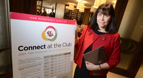Nancy Sloane, director of membership and marketing at the Center Club in Baltimore, displays a new promotion to attract new members. The Center Club logo adorns the dining room doors. (The Daily Record/Maximilian Franz)