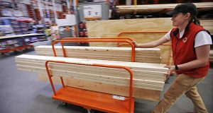 A shopper checks out with her lumber at a Home Depot in Boston. The Conference Board reports on consumer confidence in August on Tuesday, Aug. 26, 2014. (AP Photo/Gene J. Puskar)