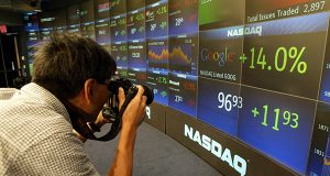 A photographer takes pictures of the board at the Nasdaq Marketsite in New York's Times Square shortly after shares of Google started trading. (AP Photo/Kathy Willens, File)