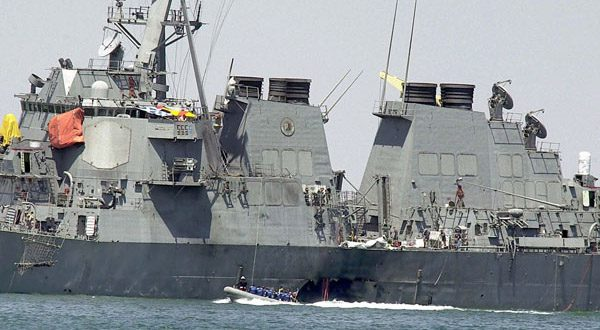 Investigators use a speed boat to examine the hull of the USS Cole at the Yemeni port of Aden, after a powerful explosion ripped a hole in the U.S Navy destroyer, in this photo from Oct. 15, 2000. (AP Photo/Dimitri Messinis, File)