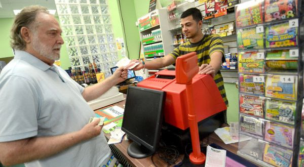 Baltimore resident Bruce Bowen, left, buys lottery tickets from Goher Khawaja, manager at Harbor Market and Deli. (The Daily Record/Maximilian Franz)