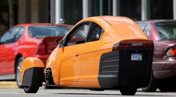 The Elio, a three-wheeled prototype vehicle, is shown in traffic in Royal Oak, Michigan. It will sell for $6,800 and gets 84 mpg. (AP Photo)