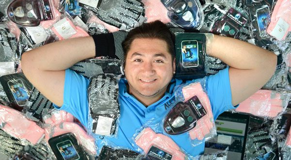 Alex Swenson, owner and founder of Team Extreme Marketing, Maryland's fastest-growing business, lies in a pile of some of his best-selling products. (The Daily Record/Maximilian Franz)