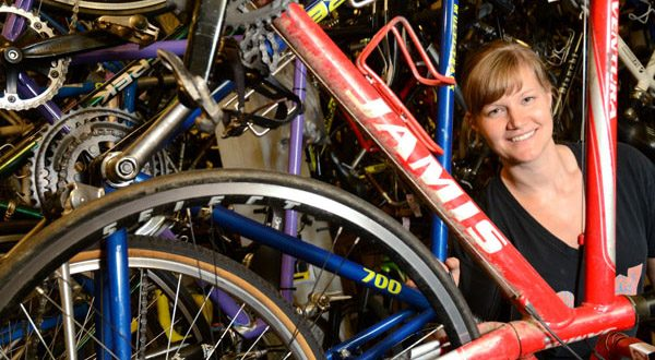 Part owner Meredith Mitchell poses among the bikes for sale at Baltimore Bicycle Works. (The Daily Record/Maximilian Franz)