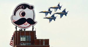 The Navy Blue Angels fly past the Natty Boh sign on Brewers Hill during their appearance in Baltimore for the Star-Spangled Spectacular. (The Daily Record/Maximilian Franz)